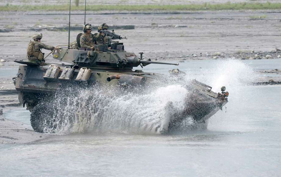 US Marines and their Philippine counterparts maneuver an amphibious armored personnel carrier through water at Crow Valley, Tarlac province in northern Philippines. Photo: JAY DIRECTO, AFP/Getty Images / AFP