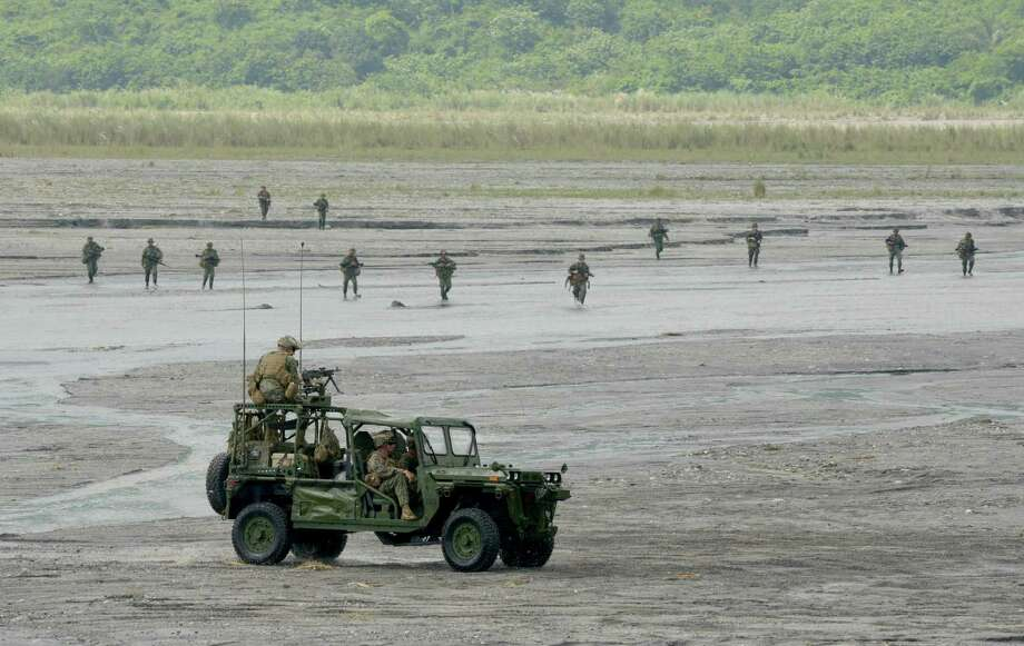 US Marines drive a jeep as officers walk (back) in wetlands at Crow Valley, Tarlac province in northern Philippines. Photo: JAY DIRECTO, AFP/Getty Images / AFP