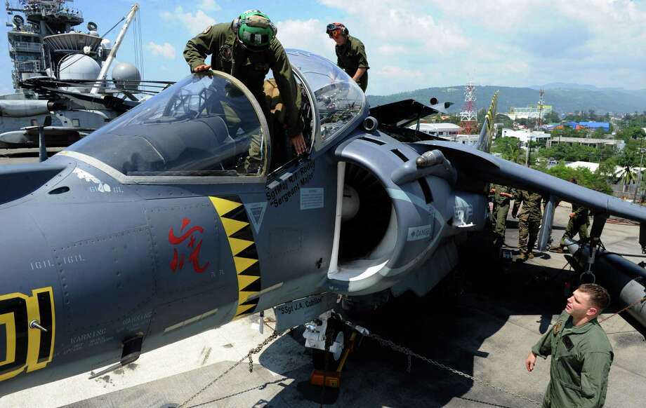 Aircraft mechanics repair a harrier jet on deck the USS Bonhomme Richard after the formal opening of the annual Philippine-US Amphibious Landing Exercises program aboard the USS Bonhomme Richard which docked at the former US naval base of Subic on October 8, 2012. Photo: JAY DIRECTO, AFP/Getty Images / AFP