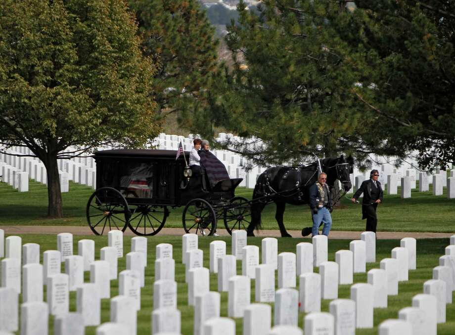 A horse drawn carriage carries the casket and remains at funeral services for Marine PFC James Jacques at Fort Logan National Cemetery in Denver on Tuesday, Oct. 9, 2012. Photo: Ed Andrieski, Associated Press / AP