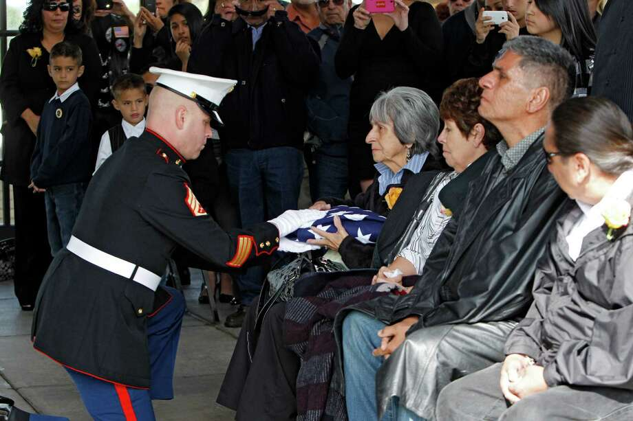 Delouise Guerra the sister of Marine  PFC James Jacques is presented the flag that draped his casket at Fort Logan National Cemetery in Denver on Tuesday, Oct. 9, 2012. Photo: Ed Andrieski, Associated Press / AP