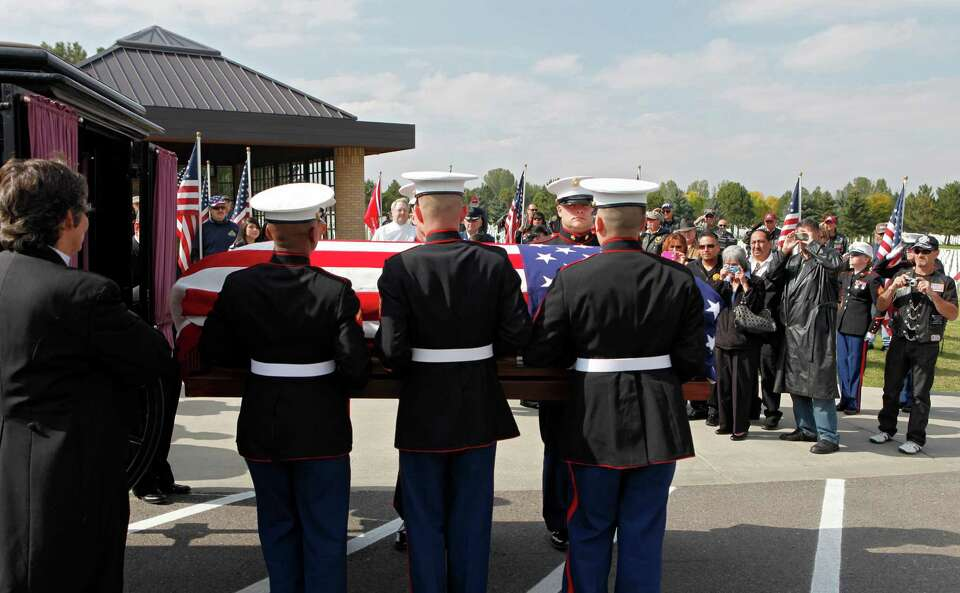 A Marine  honor guard removes the casket and remains of Marine  PFC James Jacques from a carriage at