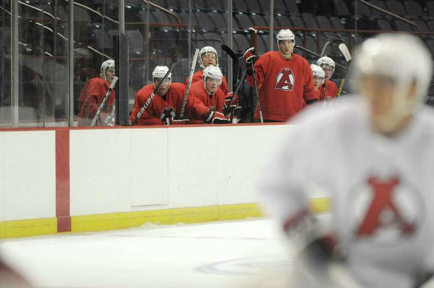 Players in the box wait for their turn on the ice  during the Albany Devils hockey practice at the T