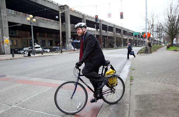"The law doesn't require that. Bike advocates say the safest way to approach a marked crossing is the same for all users: slow, determine that approaching drivers have sufficient time to stop, then enter the crossing and complete a crossing maneuver. Section 46.61.235 of the Revised Code of Washington states, ""No pedestrian or bicycle shall suddenly leave a curb or other place of safety and walk, run, or otherwise move into the path of a vehicle which is so close that it is impossible for the driver to stop."" Photo: Seattlepi.com File"