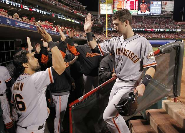 The Giants' Buster Posey, (right) scores the go ahead run in the tenth inning on a single by teammate Joaquin Arias, as the San Francisco Giants go on to beat the Cincinnati Reds 2-1,  in game three of the National League Division Series in Cincinnati, Ohio on Tuesday Oct. 9, 2012. Photo: Michael Macor, The Chronicle