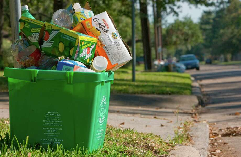 A full recycle container sits on the curb in the 4900 block of Oak Forest in northwest Houston. The city of Houston's curbside recycle program is still on hold while the city continues to focus on removal of vast amounts of storm debris. Areas such as the Oak Forest subdivision does not yet have their recycling restored.   (Thursday, Oct. 9, 2008, in Houston. ( Steve Campbell / Houston Chronicle) Photo: Steve Campbell / Houston Chronicle