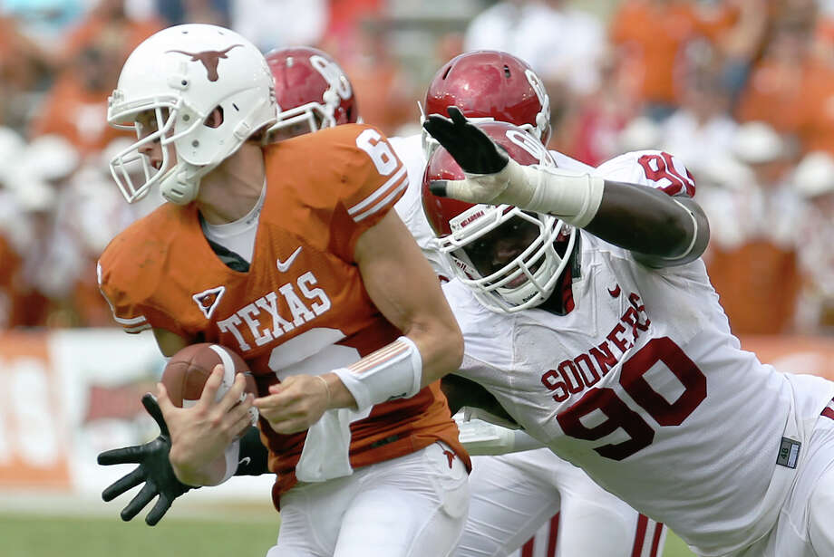 Oklahoma's David King pressures Texas' Case McCoy in last year's Red River Rivalry, a 55-17 win for OU. Photo: KIN MAN HUI / SAN ANTONIO EXPRESS-NEWS