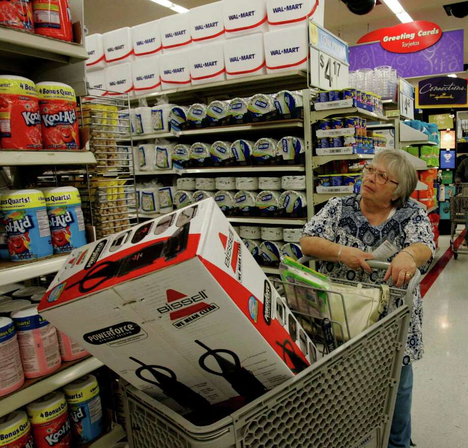 FILE-In this May 16, 2006, file photo, Nina Wilson shops at Wal-Mart in Paramount, Calif. Wal-Mart annoucned Tuesday, Oct. 9, 2012, it is testing a same-day delivery service in select markets for customers who buy popular items online during the holiday shopping season. The move comes as the world's largest retailer faces increasing competition from online giants like Amazon.com., which is testing same-day delivery service in 10 markets. (AP Photo/Nick Ut, File) Photo: NICK UT / AP