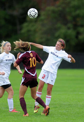 Fairfield Warde's Sarah Reilly heads the ball as St. Joseph's Jenna Bike defends during their soccer match Tuesday, Oct. 9, 2012 at Fairfield Warde High School. Photo: Autumn Driscoll / Connecticut Post