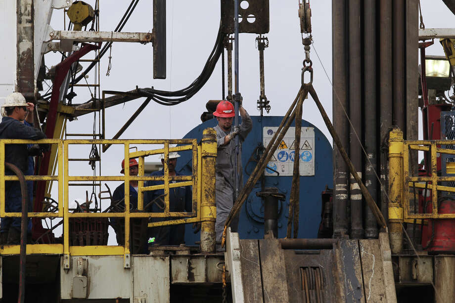 Oil workers tend to a rig over the Eagle Ford Shale formation near Tilden. Such wells extract oil and natural gas through the use of hydraulic fracturing. Photo: JOHN DAVENPORT, Jdavenport@express-news.net / jdavenport@express-news.net