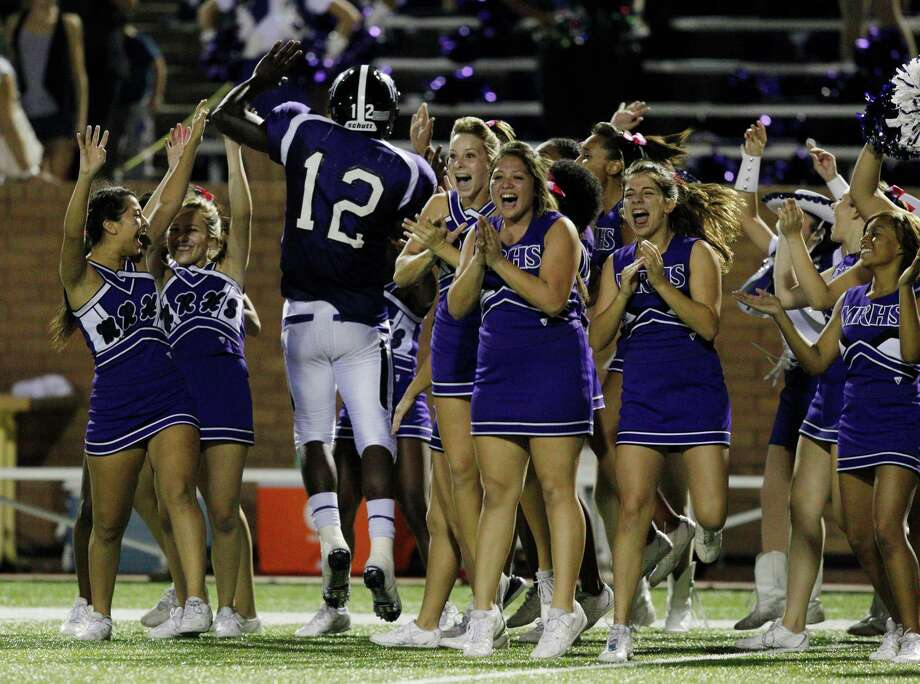 Morton Ranch quarterback Quandre Washington #12 celebrates with the cheerleaders after defeating Cinco Ranch during a high school football game between Morton Ranch and Cinco Ranch at Rhodes Stadium October 5, 2012 in Katy, Texas. Morton Ranch won 38-35 in overtime. Photo: Bob Levey / ©2012 Bob Levey