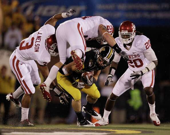 Missouri wide receiver T.J. Moe (bottom center) is tackled by Oklahoma linebacker Tom Wort (top center) cornerback Quinton Carter (right) and cornerback Jonathan Nelson (left) during the first quarter of an NCAA college football game Saturday, Oct. 23, 2010, in Columbia, Mo. Photo: Jeff Roberson, Associated Press / AP