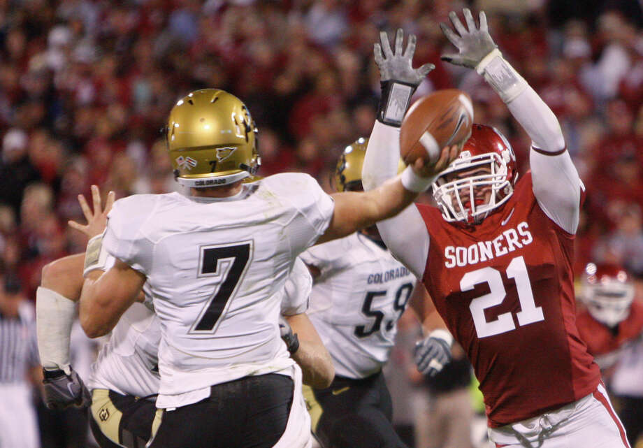 Colorado quarterback Cody Hawkins (left) passes under pressure from Oklahoma linebacker Tom Wort (right) in the third quarter of an NCAA college football game in Norman, Okla., Saturday, Oct. 30, 2010. Oklahoma won 43-10. Photo: Sue Ogrocki, Associated Press / AP