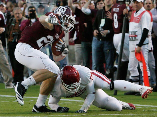 Texas A&M wide receiver Ryan Swope (25) keeps his balance after making a catch on a pass from Texas A&M quarterback Ryan Tannehill (not pictured) as Oklahoma linebacker Tom Wort (21) tries to make the tackle near the 5-yard line in the first quarter of an NCAA Football game between Texas A&M and Oklahoma at Kyle Field on Saturday, Nov. 6, 2010, in College Station. Photo: Julio Cortez, Houston Chronicle / © 2010 Houston Chronicle