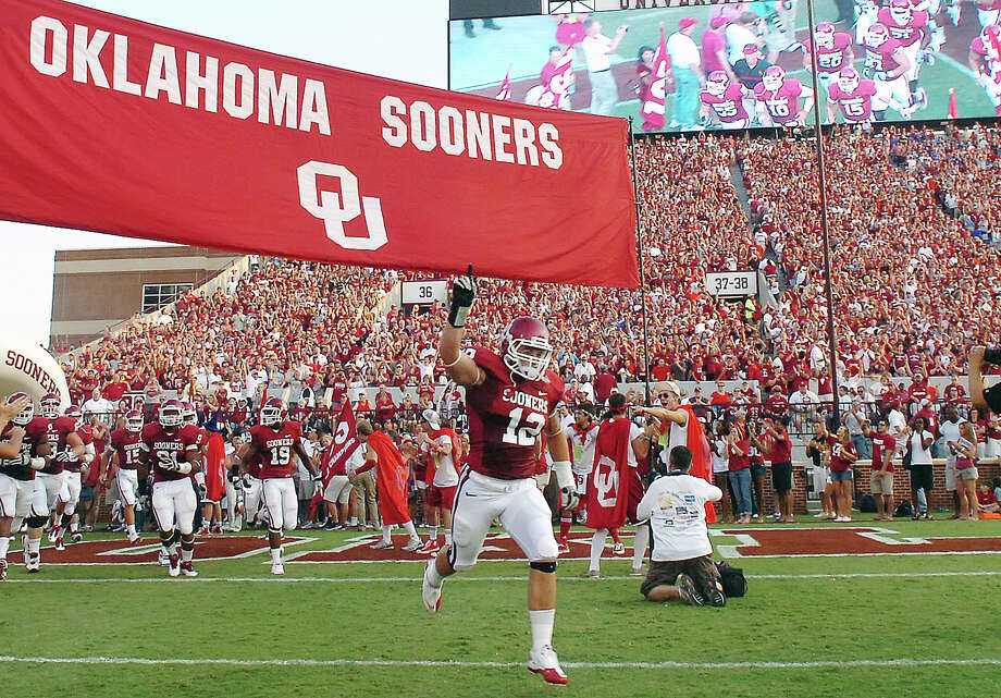 Oklahoma's Tom Wort, wearing jersey No. 12 in honor of teammate Austin Box, leads the Sooners onto the field for the season NCAA college football game opener against Tulsa, Saturday, Sept. 3, 2011, on Owen Field in Norman, Okla. Oklahoma beat Tulsa 47-14. Box overdosed on painkillers in May. Wort became the first in a series of defenders that will wear his number as a tribute this season. Photo: Billy Hefton, Associated Press / Enid News & Eagle