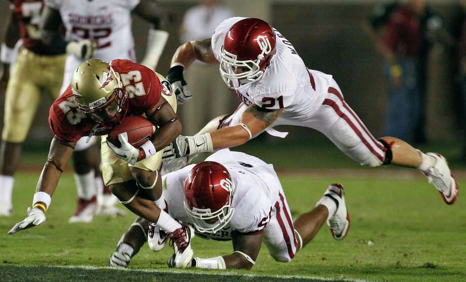 Florida State running back Chris Thompson (23) eludes a tackle by Oklahoma linebacker Tom Wort (21) and defensive end Ronnell Lewis (56) during the second quarter of an NCAA college football game Saturday, Sept. 17, 2011, in Tallahassee, Fla. Photo: Chris O'Meara, Associated Press / AP