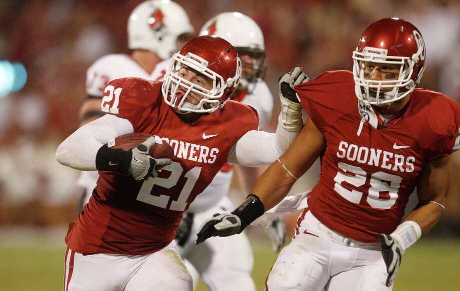 Oklahoma linebacker Tom Wort (left) returns a Ball State fumble for a touchdown in the third quarter of an NCAA college football game in Norman, Okla., Saturday, Oct. 1, 2011. Oklahoma won 62-6. Oklahoma's Travis Lewis is at right. Photo: Sue Ogrocki, Associated Press / AP