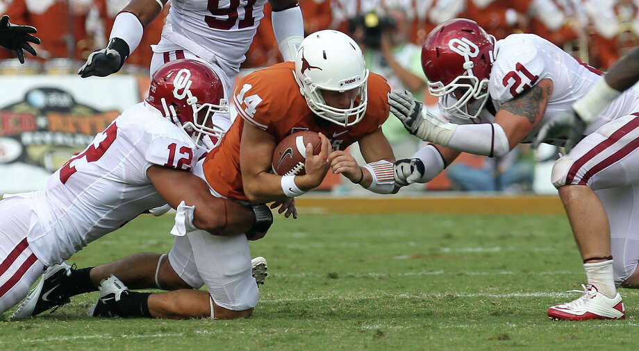 Oklahoma's Travis Lewis (12) and Tom Wort (21) tackle Texas quarterback David Ash (14) in the second half of the Red River Rivalry at the Cotton Bowl in Dallas on Saturday, Oct. 8, 2011. The Sooners defeated the Longhorns, 55-17. Photo: Kin Man Hui, San Antonio Express-News / San Antonio Express-News
