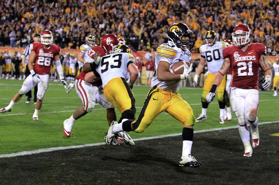 Iowa's Jordan Canzeri (33) scores a touchdown ahead of Oklahoma's Tom Wort (21) in the fourth quarter in the Insight Bowl NCAA college football game Friday, Dec. 30, 2011, in Tempe, Ariz. Oklahoma defeated Iowa 31-14. Photo: Ross D. Franklin, Associated Press / AP