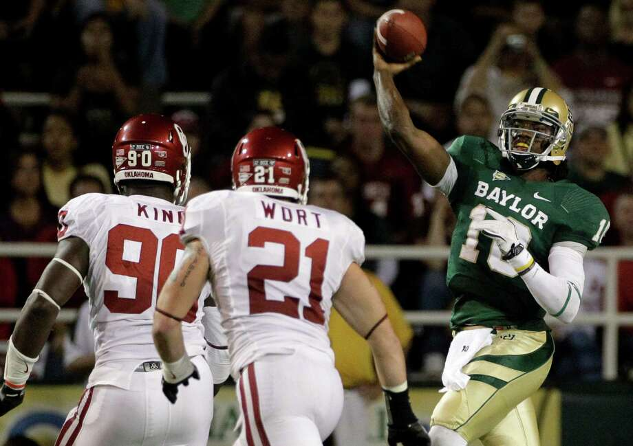 Oklahoma defensive end David King (90) and linebacker Tom Wort (21) give chase as Baylor quarterback Robert Griffin III (10) passes in the first half of an NCAA college football game on Saturday, Nov. 19, 2011, in Waco. Photo: Tony Gutierrez, Associated Press / AP