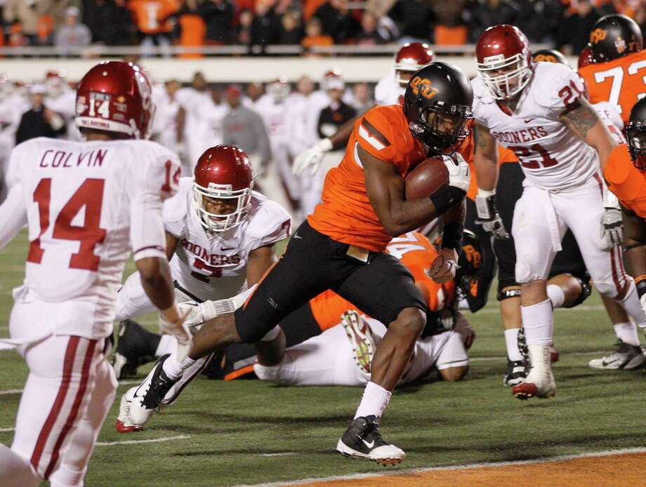 Oklahoma State running back Joseph Randle (center) scores past Oklahoma defenders defensive back Aaron Colvin (14), linebacker Corey Nelson (7) and linebacker Tom Wort (21) in the second quarter of an NCAA college football game in Stillwater, Okla., Saturday, Dec. 3, 2011. Photo: Sue Ogrocki, Associated Press / AP