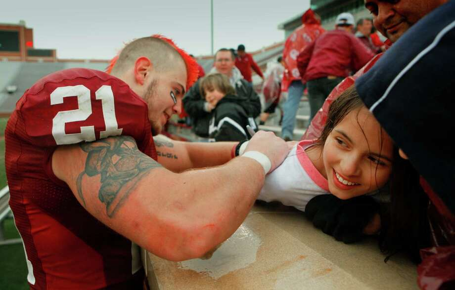 Tom Wort (21) autographs the shirt of Kaysia Lopez of Salina, Kansas, following the spring Red and White football game for the University of Oklahoma (OU) Sooners at Gaylord Family -- Oklahoma Memorial Stadium on Saturday, April 17, 2010, in Norman, Okla. Photo: Steve Sisney, The Oklahoman / THE OKLAHOMAN