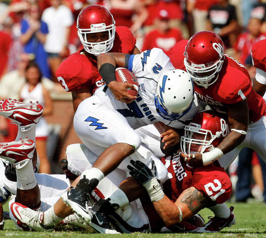 Air Force quarterback Tim Jefferson (center) is tackled by Oklahoma defensive back Jonathan Nelson (left) defensive back Tony Jefferson (right) and linebacker Tom Wort (bottom right) in the first quarter of an NCAA college football game in Norman, Okla., Saturday, Sept. 18, 2010. Photo: Sue Ogrocki, Associated Press / AP