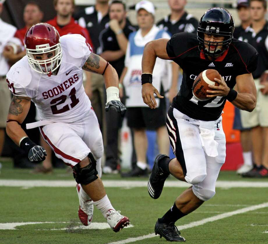Cincinnati quarterback Zach Collaros (right) is pursued by Oklahoma linebacker Tom Wort (21) in the first half of an NCAA college football game, Saturday, Sept. 25, 2010, in Cincinnati. Photo: Tom Uhlman, Associated Press / FR31154 AP