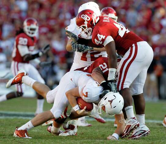 "Texas Longhorns cornerback A.J. White (7) is sacked by Oklahoma Sooners linebacker Tom Wort (21) and Oklahoma Sooners defensive end Jeremy Beal (44) during second half NCAA Big 12 ""Red River Shootout"" football action between the University of Texas and the University of Oklahoma at the Cotton Bowl on Oct. 2, 2010. Oklahoma won 28-20. Photo: John F. Rhodes, Dallas Morning News / 10005527C"