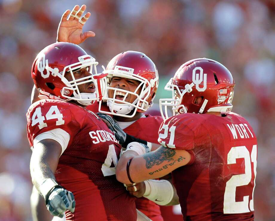 Oklahoma Jeremy Beal (44) is congratulated by teammates Tom Wort (21) and Pryce Macon (94) during the second half of play at the Red River Rivalry at the Cotton Bowl at Fair Park in Dallas on Oct. 2, 2010. Oklahoma defeated Texas 28-20. Photo: Vernon Bryant, Dallas Morning News / 10005527D