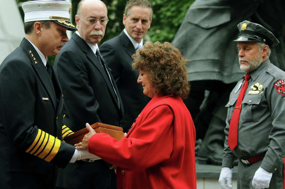 Rita Akin, center, receives a flag in honor of her deceased husband, William E. Akin Jr., during the New York State Fallen Firefighters Memorial Ceremony on Tuesday, Oct. 9, 2012, at the Empire State Plaza in Albany, N.Y. Akin was a firefighter with the Ghent Volunteer Fire Company. (Cindy Schultz / Times Union)