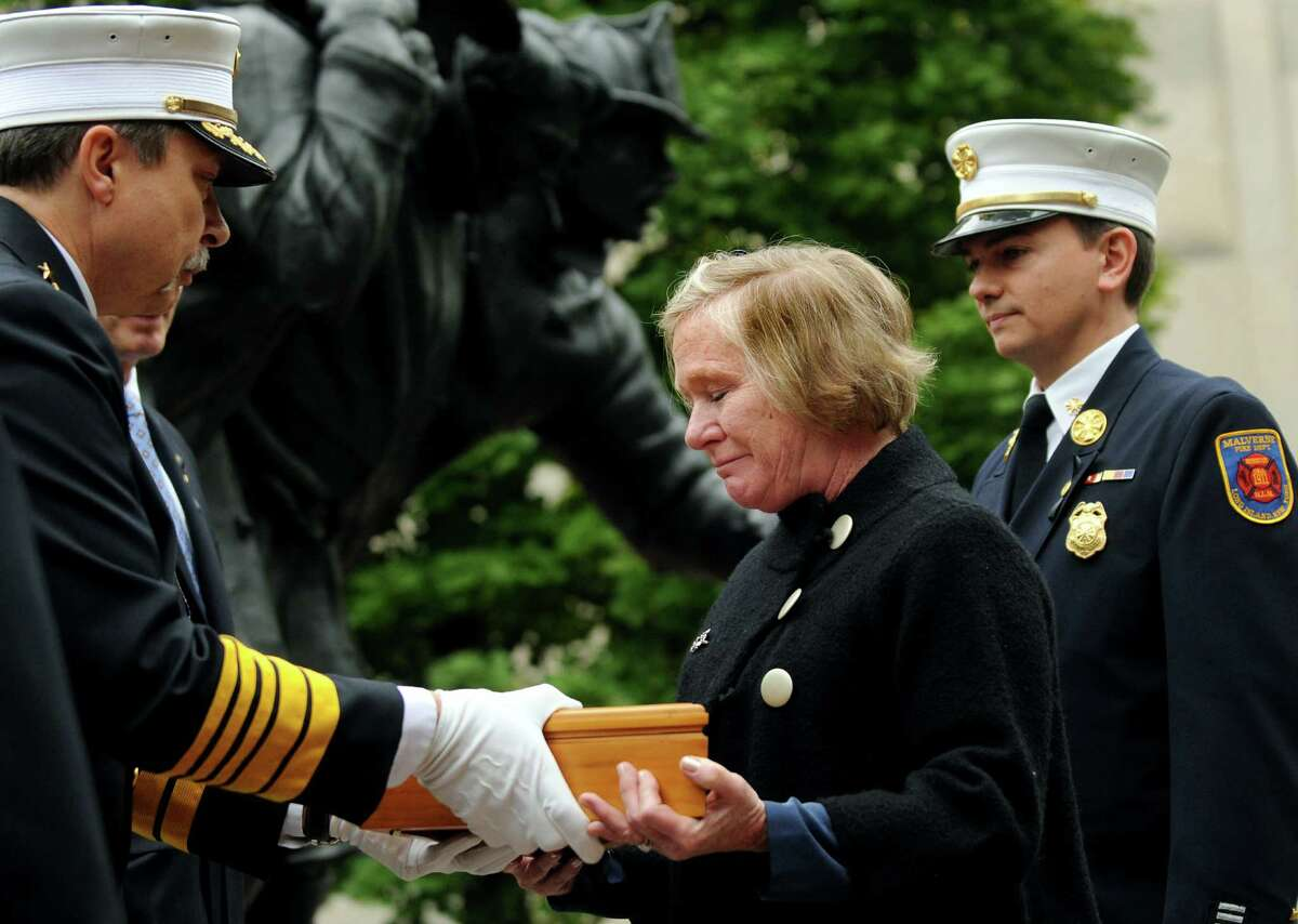 Barbara Pierce, center, receives a flag in honor of her brother Paul Brady during the New York State Fallen Firefighters Memorial Ceremony on Tuesday, Oct. 9, 2012, at the Empire State Plaza in Albany, N.Y. Brady was a firefighter with the Malverne Volunteer Fire Department. (Cindy Schultz / Times Union)