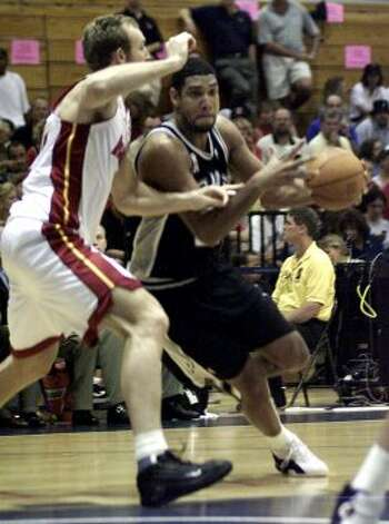 The Spurs' Tim Duncan (right) drives to the basket past the Heat's Sean Marks (left) in a preseason game at Florida Atlantic University in Boca Raton, Fla., Tuesday, Oct. 23, 2001. (Associated Press file photo)