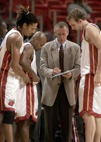 Miami Heat head coach Pat Riley (second from right) goes over plays with forward Brian Grant (left) guard Travis Best (second from left) and forward Sean Marks during the first half of a preseason game against the Detroit Pistons on Tuesday, Oct. 22, 2002, in Miami. (Wilfredo Lee / Associated Press)