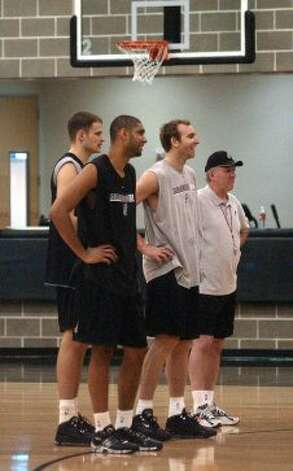 Spurs players Radoslav Nesterovic (from left), Tim Duncan and Sean Marks enjoy a light moment with Coach Gregg Popovich during practice on Friday, Jan. 2, 2004. The Spurs are riding a 13-game winning streak. (Billy Calzada / San Antonio Express-News)