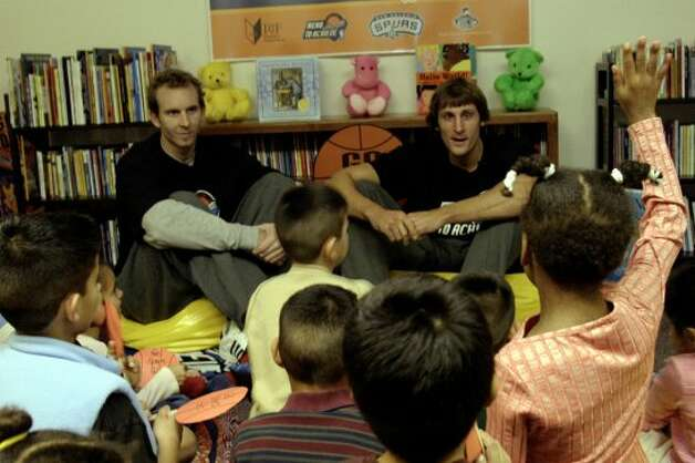 "Spurs center Sean Marks (left) and guard Brent Barry (right) read the book ""Sylvester and the Magic Pebble,"" by author William Steig, and talk about reading to children at the San Antonio Children's Center on Monday, Nov. 15, 2004. (J. Michael Short / For the Express-News)"