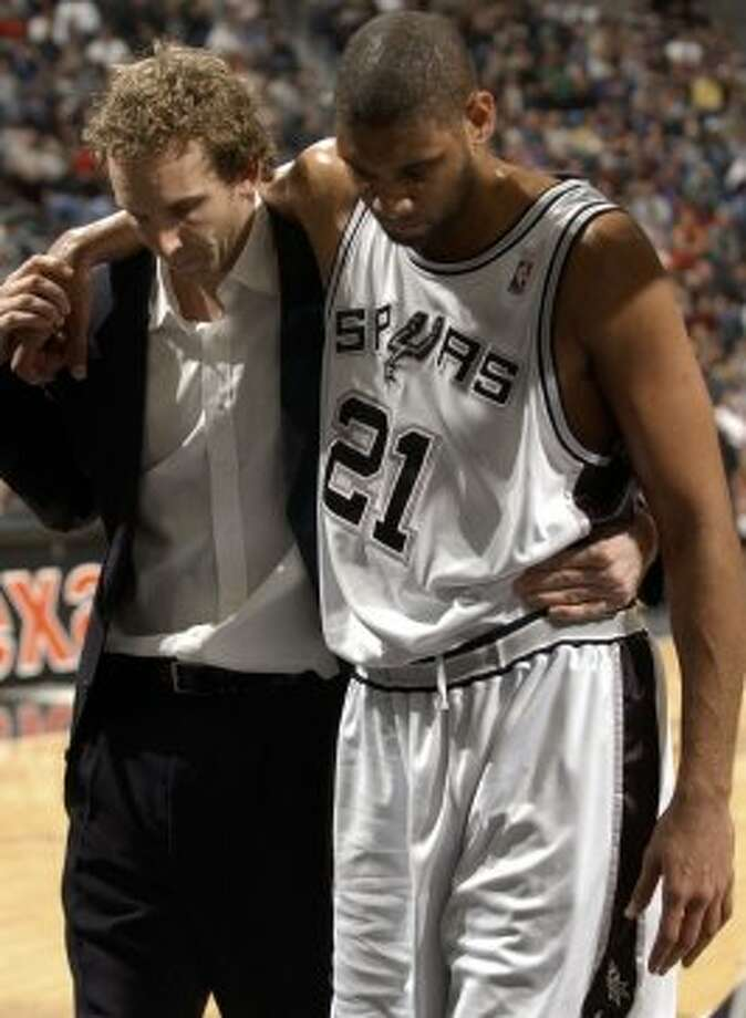 The Spurs' Sean Marks (left) helps teammate Tim Duncan off the court. Duncan suffered a sprained right ankle during the game with the Jazz on Sunday March 6, 2005, at the SBC Center. (Edward A. Ornelas / San Antonio Express-News)