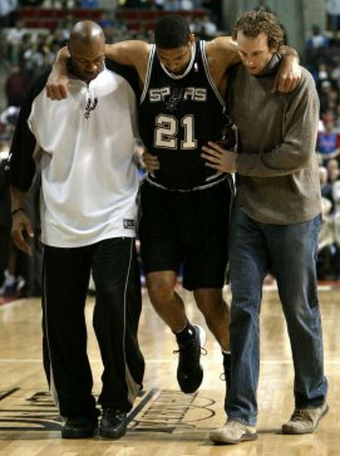 The Spurs' Tim Duncan is helped off the court by Tony Massenburg (left) and Sean Marks (right) after turning his right ankle against the Detroit Pistons in the first quarter in Auburn Hills, Mich., Sunday, March 20, 2005. Duncan was helped to the locker room without putting weight on his right foot. Duncan missed two games earlier this month with a sprained right ankle. (Paul Sancya / Associated Press)