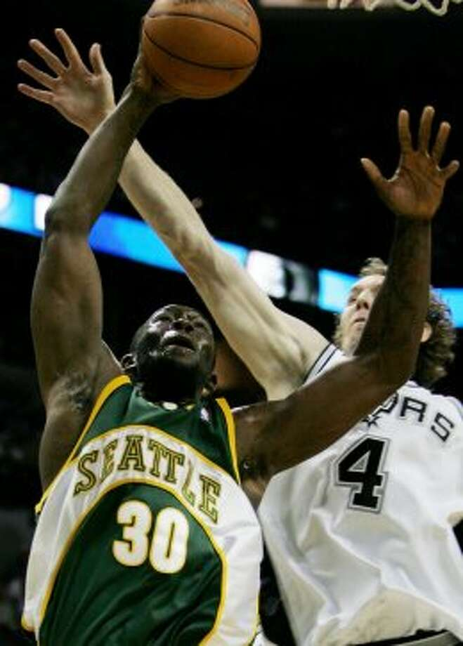 Seattle SuperSonics forward Reggie Evans (30) is fouled by Spurs defender Sean Marks (4) as he tries to score during the first quarter in San Antonio, Wednesday, March 30, 2005. (Eric Gay / Associated Press)