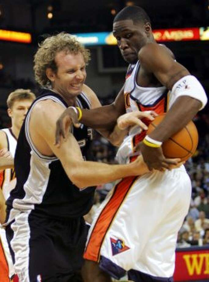 The Golden State Warriors' Mickael Pietrus (right) fights for a rebound against the Spurs' Sean Marks in the first half in Oakland, Calif., on Sunday, April 10, 2005. (Marcio Jose Sanchez / Associated Press)