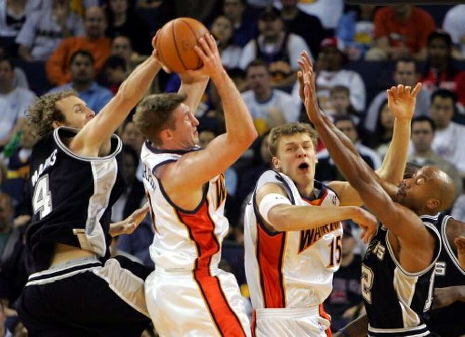 The  Spurs' Sean Marks (from left), the Golden State Warriors' Troy Murphy and Andris Biedrins and the Spurs' Bruce Bowen fight for a rebound in the first half in Oakland, Calif., on Sunday, April 10, 2005. (Marcio Jose Sanchez / Associated Press)