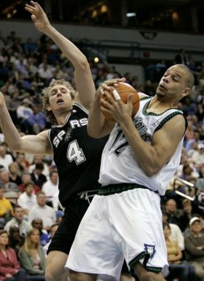 Timberwolves forward John Thomas (right) pulls down a rebound against Spurs forward Sean Marks during the second quarter in Minneapolis, Wednesday, April 20, 2005. (Ann Heisenfelt / Associated Press)