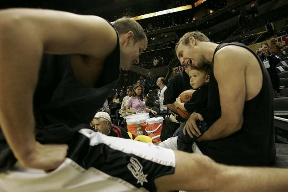 Rasho Nesterovic (left) visits with fellow Spur Sean Marks and his son, Aidan Marks, 21 months, before Game 6 of the NBA Finals at the SBC Center on June 21, 2005. Marks is not on the playoff roster. (Lisa Krantz / San Antonio Express-News)