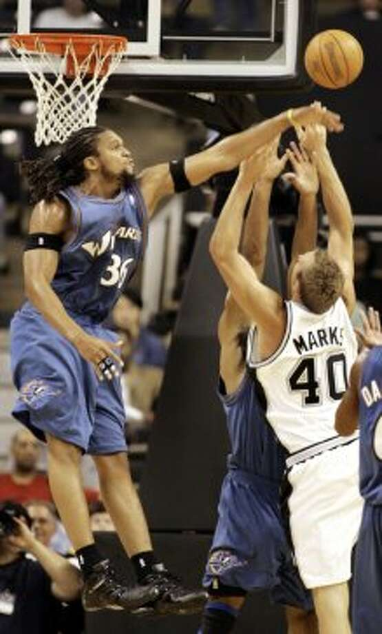 The Wizards' Michael Ruffin (back right) and Etan Thomas (left) defend on a shot by the Spurs' Sean Marks in a preseason game Thursday, Oct. 13, 2005, in Winston-Salem, N.C. (Lynn Hey / Associated Press)