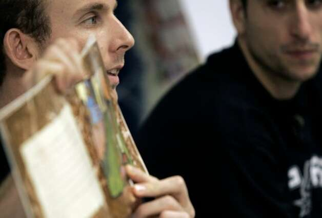 "Spurs player Manu Ginobili looks on as teammate Sean Marks reads a book about an unlikely Olympic gold medalist to fifth-graders at Loma Park Elementary School on Monday, Jan. 23, 2006. The players were invited to commemorate the ""What'cha Reading Contest winner Joaquin Calderon, 11. (Mike Kane / San Antonio Express-News)"