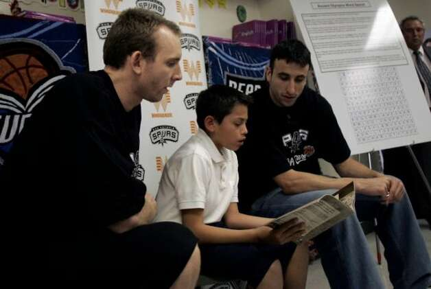 "Spurs players Manu Ginobili (right) and Sean Marks watch as ""What'cha Reading"" contest winner Joaquin Calderon, 11, reads a book about an unlikely Olympic gold medalist to his 5th grade class at Loma Park Elementary School on Monday, Jan. 23, 2006.  (Mike Kane / San Antonio Express-News)"