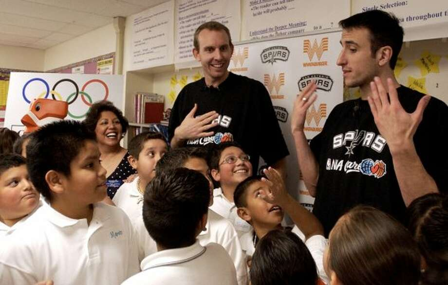 """Spurs players Manu Ginobili and Sean Marks prepare to pose for a picture with fifth-graders at Loma Vista Elementary School. Ginobili and Marks visited the school because Joaquin Calderon is the grand prize winner of the Spurs/Whataburger """"What'cha Reading"""" contest. Ginobili and Marks read to the kids and helped them complete a word find on Monday, Jan. 23, 2006. (Helen L. Montoya / San Antonio Express-News)"""