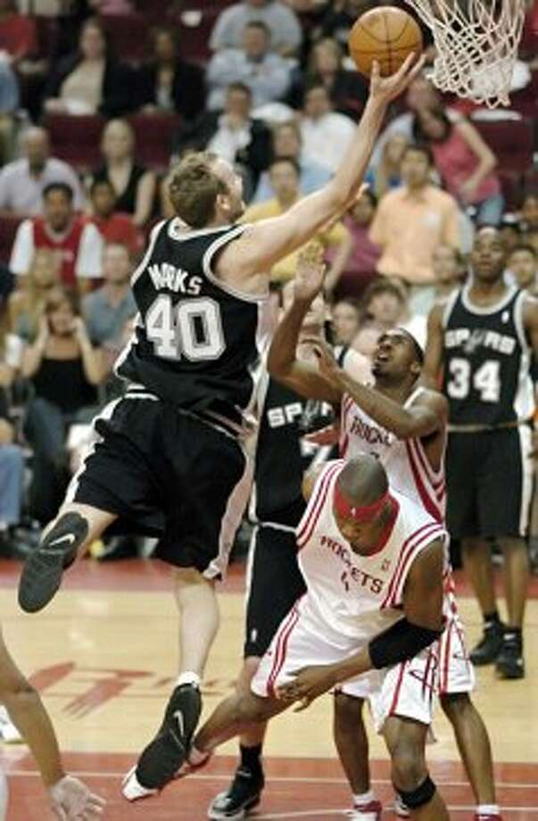 The Spurs' Sean Marks (40) drives and scores over the Rockets' Stromile Swift (4) and Luther Head (rear) in the final minute of their basketball game Wednesday, April 19, 2006, in Houston. The Rockets lost to the Spurs 89-87. (Tim Johnson / Associated Press)