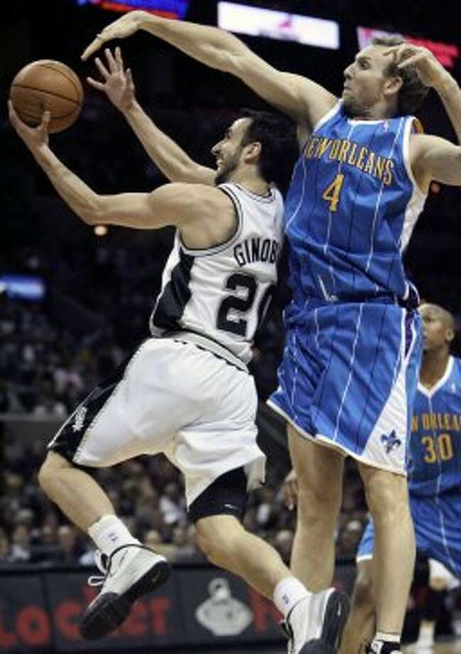 Spurs guard Manu Ginobili gets to the hoop under Hornets center Sean Marks as the Spurs host New Orleans at the AT&T Center Saturday, Jan. 31, 2009. (Tom Reel / San Antonio Express-News)