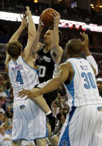Spurs guard Manu Ginobili (20) goes for a shot between Hornets forwards Sean Marks (left) and David West during the first half of an NBA basketball game Sunday, March 29, 2009, in New Orleans. (Brian Lawdermilk / Associated Press)